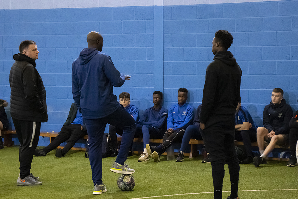 Yaya Toure talking to the students sitting on the bench