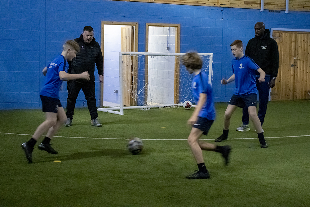 Students tackling each other as coaches look on