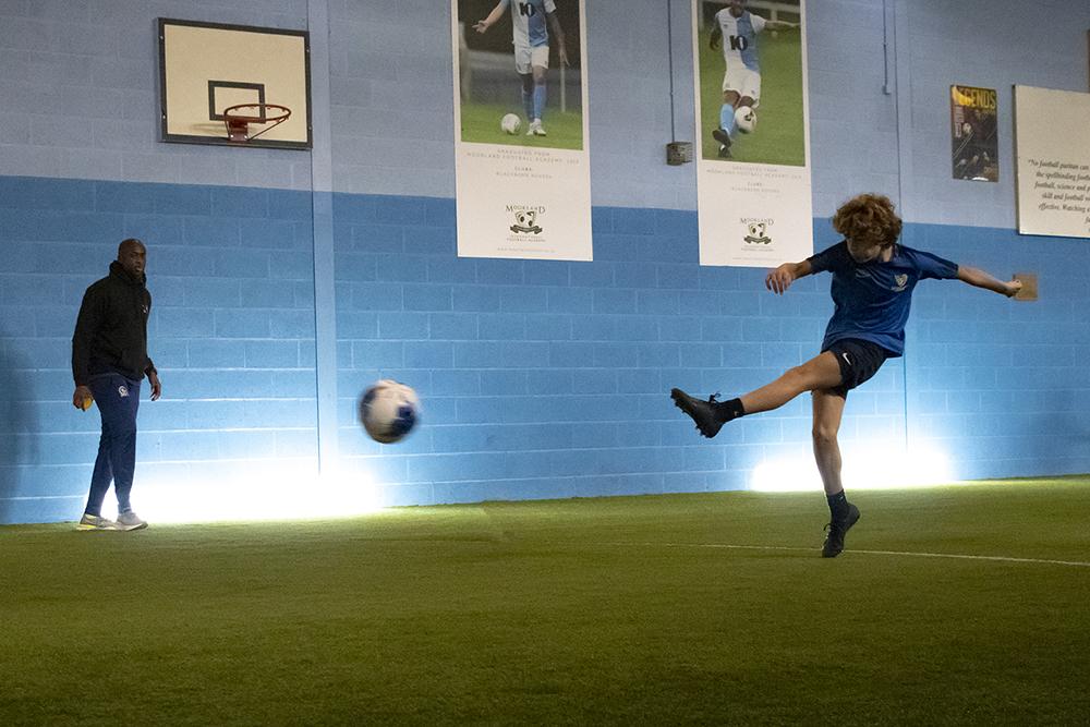 Student kicking ball and Yaya Toure looking on