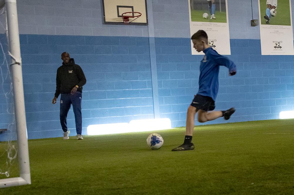 Student kicking ball into goal as Yaya Toure watches