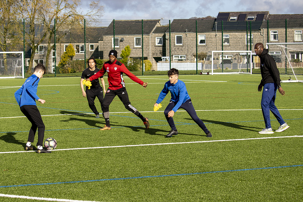 Yaya Toure and students playing on the pitch