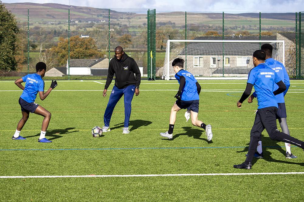 Students and Yaya Toure playing football