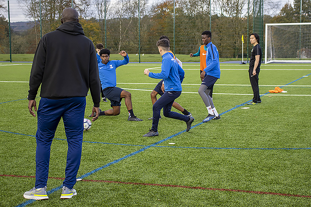 Students playing as coach watches