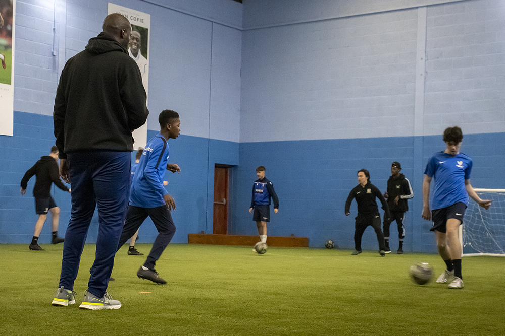 Student passing football with coach watching