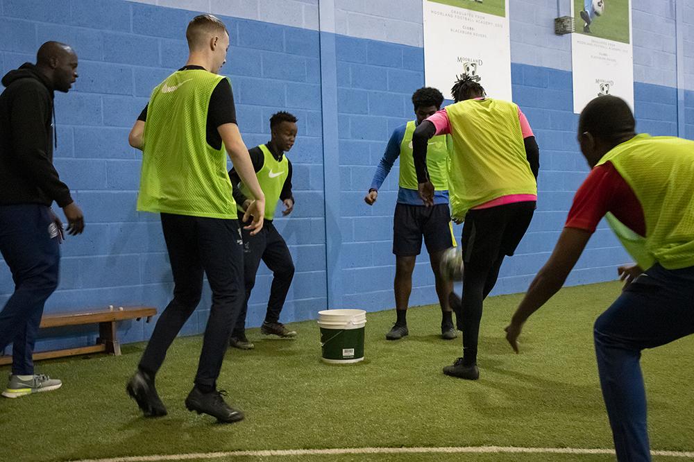 Boys around a bucket trying to kick ball inside