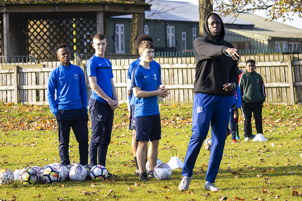Yaya Toure pointing as students listen