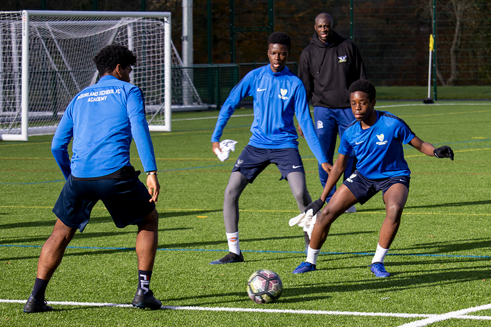 Students playing a game of football with Yaya Toure