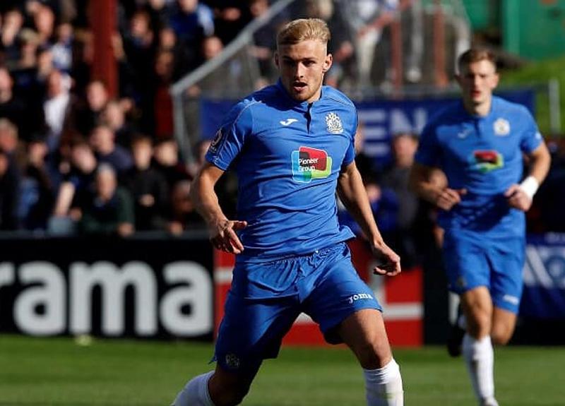 Footballer Alex Curran running on pitch