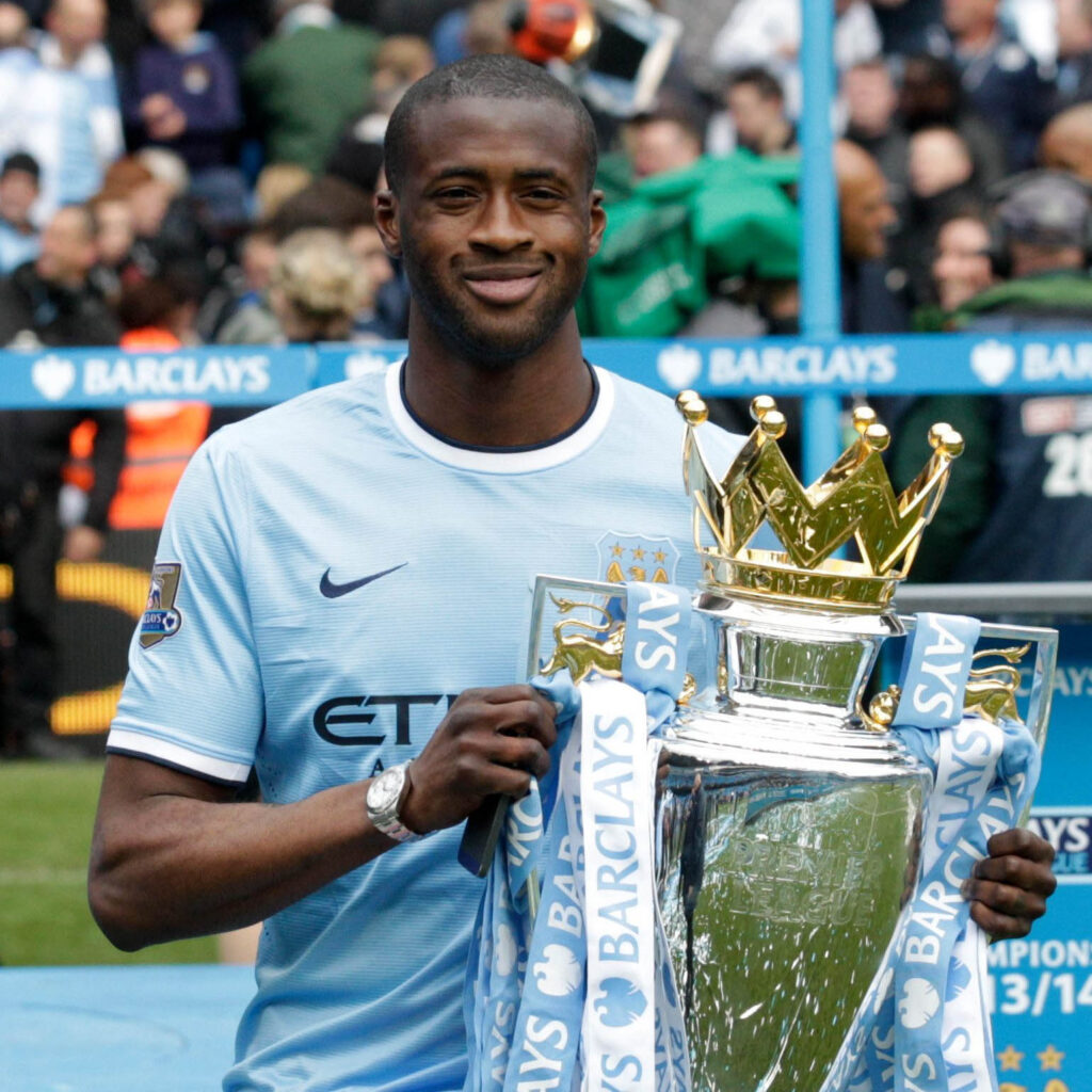 Yaya Toure smiling and holding Premier League trophy